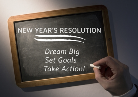 paper wad: Hand writing new year resolution goals on slate board