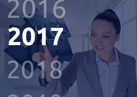 Smiling business woman in digitally generated background touching 2017 new year