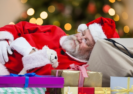 Tired Santa claus sleeping on gift boxes