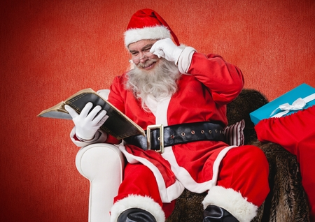 mature adult: Santa claus sitting on chair and reading bible Stock Photo