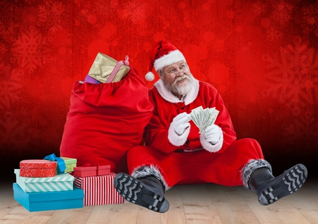 Santa claus holding banknotes sitting by gift bag against red background