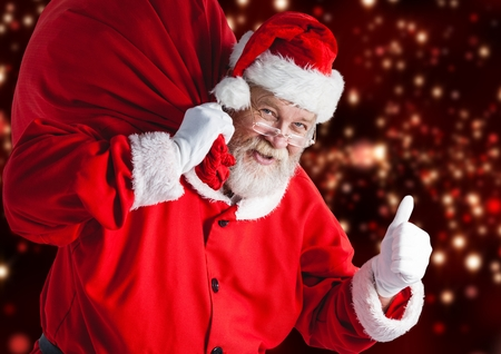 Portrait of santa claus carrying gift bag showing thumbs up sign