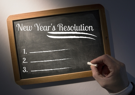 motivated: Hand writing list of new year resolution goals on slate board