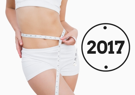 waist: Mid section of woman measuring her waist against 2017 Stock Photo