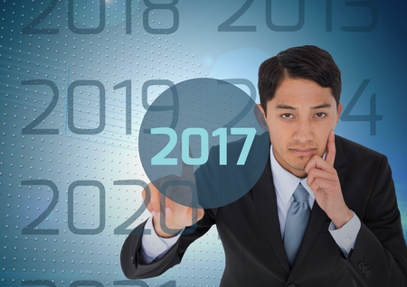 thoughtful: Portrait of thoughtful business man in digitally generated background touching 2017 new year