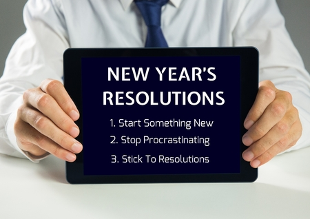 motivated: Man holding a digital tablet showing list of new year resolution goals