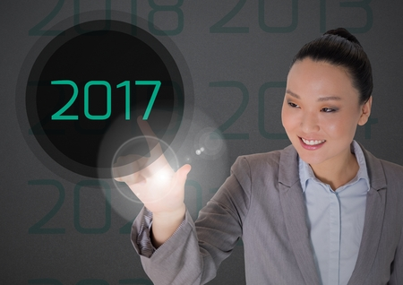 happy business woman: Smiling business woman in digitally generated background touching 2017 new year