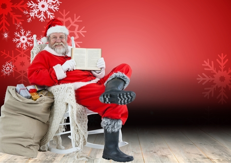 Portrait of santa claus sitting on chair with gifts and showing bible
