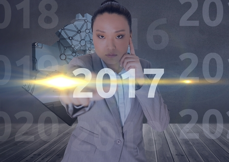 Portrait of business woman in digitally generated background touching 2017 new year message