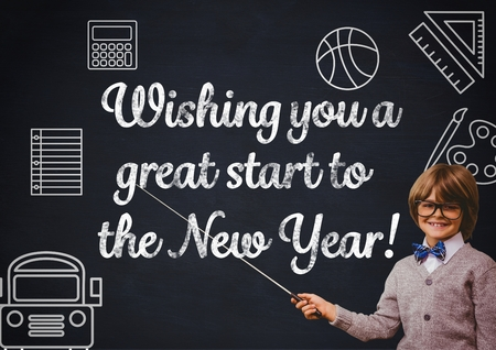 Portrait of smiling boy pointing at blackboard with new year greeting quotes