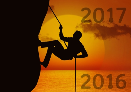 Composite image of 2017 with silhouette of man climbing a cliff using rope during sunset