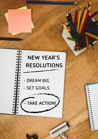 it is full: List of new year resolution goals with office supplies on wooden table Stock Photo