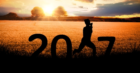 Silhouette of a running person forming 2017 new year sign during sunrise Stock Photo
