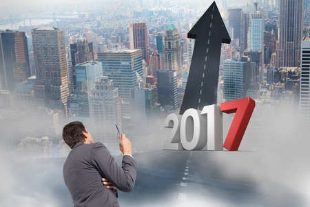 2017 against a composite image of business man looking at road leading towards sky in city