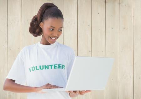 using laptop: Smiling female volunteer using laptop against wooden background