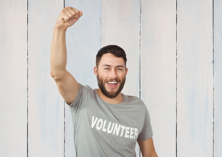 mid adult men: Volunteer raising fist to camera against wooden background Stock Photo