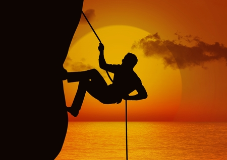 Silhouette of man climbing a cliff using rope during sunset