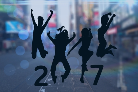 Silhouette of jumping people forming 2017 new year sign against city street in background Stock Photo