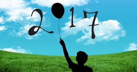 grass close up: Silhouette of boy holding balloon forming 2017 new year sign against blue sky