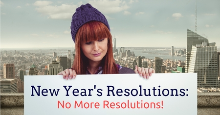 Beautiful girl holding a placard with new year resolutions against city background