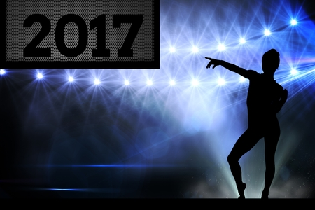 outstretched: Silhouette of woman pointing at 2017 new year sign on stage Stock Photo