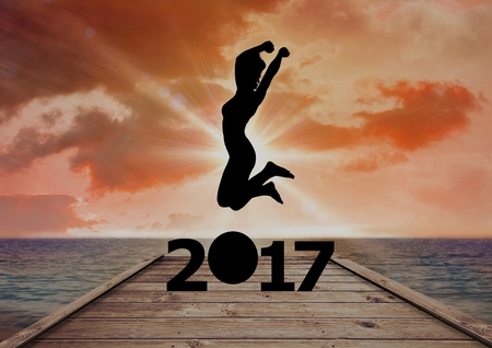 outstretched: Silhouette of woman jumping over 2017 new year sign on beach dock Stock Photo