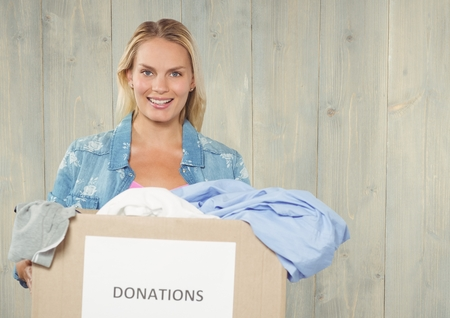 Smiling woman holding donations box against wooden background