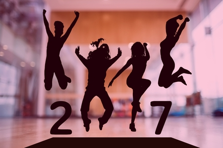 Silhouette of jumping people forming 2017 new year sign against dance studio in background