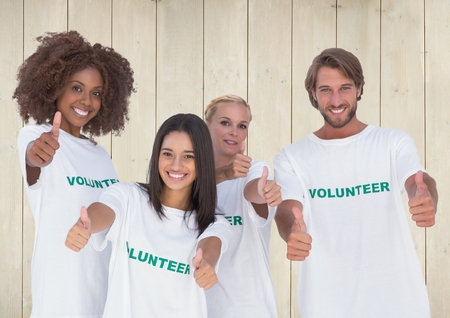 thumbs up group: Portrait of group of volunteers showing thumbs up against wooden background
