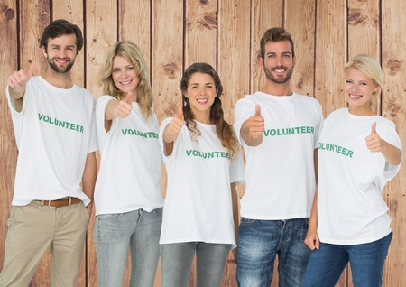 selfless: Portrait of group of volunteers showing thumbs up against wooden background