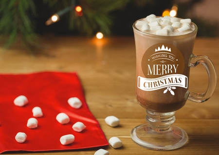 Merry Christmas greetings with coffee and marshmallow in glass on table