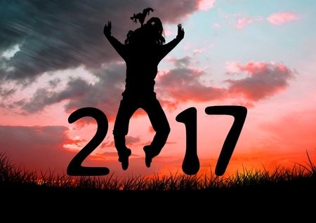 Silhouette of a jumping person forming 2017 new year sign during sunset