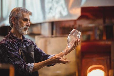 glassblower: Glassblower examining glassware at glassblowing factory