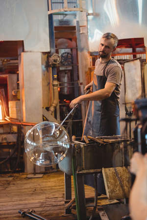 blowpipe: Glassblower shaping a glass on the blowpipe at glassblowing factory LANG_EVOIMAGES