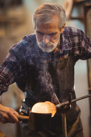 glassblower: Glassblower forming and shaping a molten glass at glassblowing factory LANG_EVOIMAGES