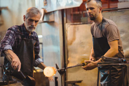 blowpipe: Team of glassblower forming and shaping a molten glass at glassblowing factory LANG_EVOIMAGES