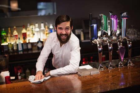 beer pump: Portrait of smiling bartender cleaning bar counter at bar