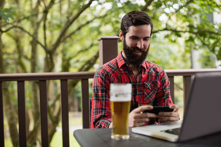 people: Man using mobile phone while sitting in bar
