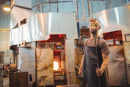 glassblower: Glassblower holding blowpipe at glassblowing factory