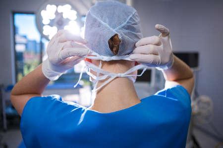 enfermera con cofia: Vista trasera de la enfermera de sexo femenino que desgasta el casquillo quirúrgico en el quirófano en el hospital