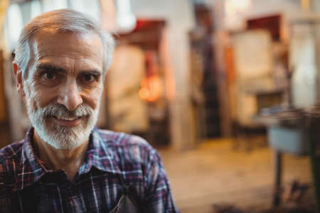 glassblower: Portrait of glassblower standing at glassblowing factory