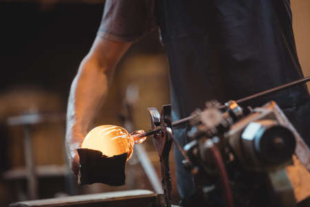 blowpipe: Mid section of glassblower forming and shaping a molten glass at glassblowing factory LANG_EVOIMAGES