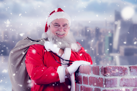 Portrait of Santa Claus with eyeglasses carrying bag full of gifts against room with large window looking on city