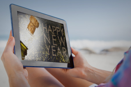 popping the cork: Woman sitting on beach in deck chair using tablet pc against close up of champagne cork popping