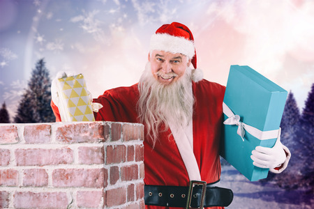 Portrait of Santa Claus placing gift boxes into chimney against snowy landscape with fir trees