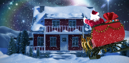 Santa Claus riding on sled with gift box against bridge on snow covered mountain against full moon Stock Photo