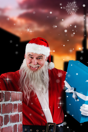 Portrait of Santa Claus placing gift boxes into chimney against cityscape during sunset Stock Photo