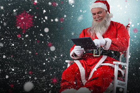 Cheerful Santa Claus using digital tablet against snow with red flakes Stock Photo