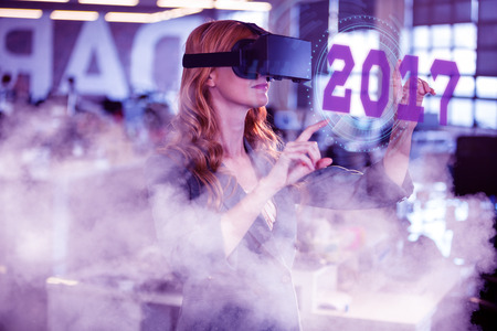 virtual reality simulator: Digital image of new year 2017 against businesswoman using virtual reality simulator