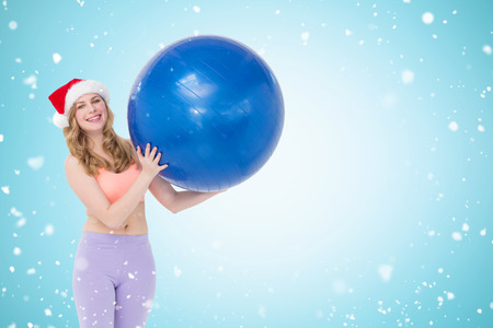 Smiling blonde woman holding exercise ball  against christmas snow falling Stock Photo